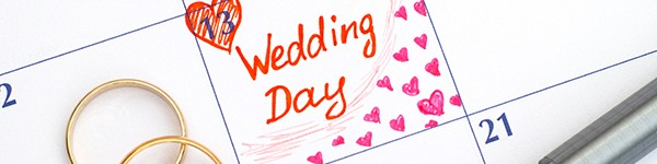 Reminder Wedding day in calendar with pen and two wedding rings.